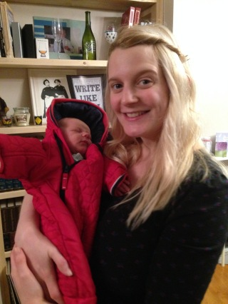 Me, blonde 26 year old wearing a black dress, holding TM - 6 day old baby- in our living room, he's in a big red snowsuit as we were about to go for a walk.