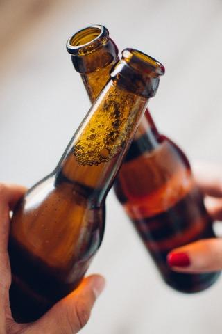 2 hands holding brown beer bottles clinking together
