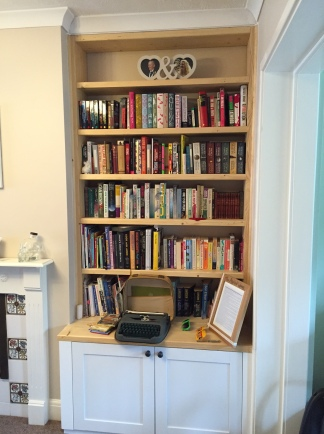 picture of a bookshelf built into the wall filled with books and with a type writer and picture on a shelf above some cupboards at the bottom