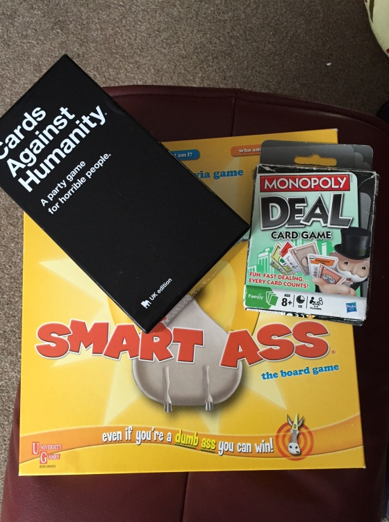 A picture of 3 games - Smart Ass, Cards Against Humanity and Monopoly Deal card game