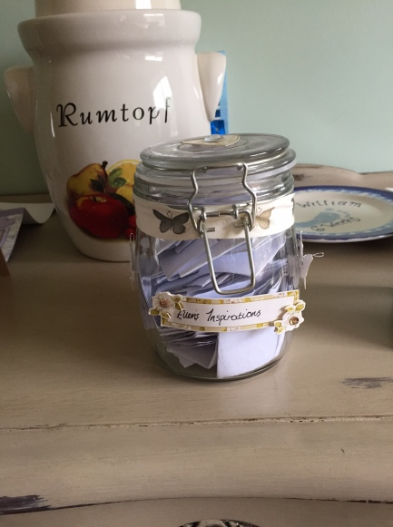 A jar with 'Ellen's inspirations' written on it with a butterfly ribbon tied round and little butterflies stuck on, filled with bits of white paper folded up