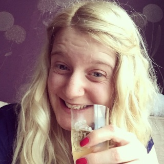 Me drinking a glass of champagne and smiling...with pink nail varnish!