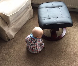TM sitting next to a black footstool wearing a babygro covered in cars
