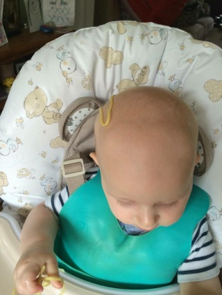 TM in his highchair with a noodle on his head