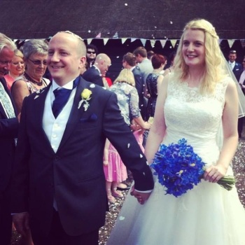 Bride and groom ( me and B) walking outside with confetti thrown on them. Lots of wedding guests visible in the background. Groom is bald and wearing a dark grey lounge suit, waistcoat, cravat and yellow buttonhole flower. He is holding hands with the bride who is walking just behind him holding a blue bouquet of delphiniums, she is blonde with curls in her hair wearing an ivory wedding dress with a lace top and a big skirt. They are both smiling.