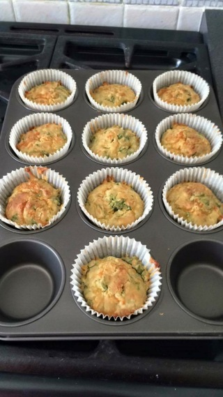 Cooked cheese and spinach muffins in a grey muffin tray
