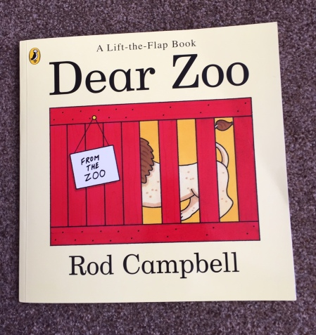 "The front cover of ""dear zoo' lift-the-flap book with a pale yellow background and an illustration of A lion partially obscured in a red cage with a note saying 'from the zoo' - by Rod Campbell"