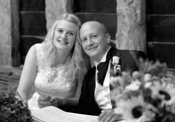 Black and white image of bride and groom (me and B) sitting down and signing register. Beams are behind them as they are in an old barn. There are flowers in the corner of the picture. The bride has a lacy-topped dress and the groom is wearing a lounge suit with waistcoat and cravat. The bride's hair is down and slightly curly and the groom is bald. They are both smiling and holding hands with the bride holding a pen over the marriage register