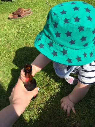 TM on the grass with a green hat on with blue stars on it reaching for a brown bottle of Bud which I am holding
