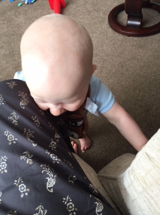 TM stood at my leg, I am wearing grey trousers with peacocks on them and he is in a light blue vest and brown bib