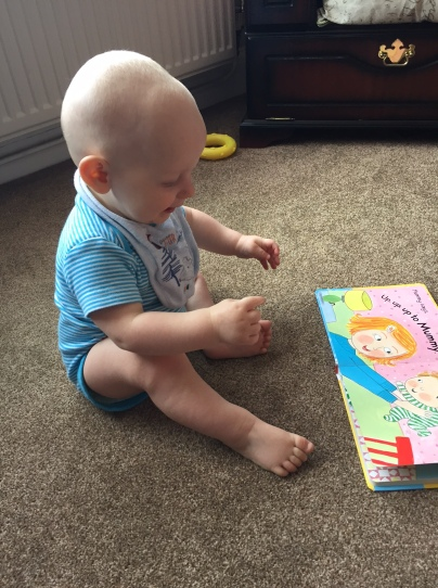 Almost bald, blond 8 month old baby in a blue stripe vest and a blue bib is sat on a beige carpet looking at an open book, where you can see a blond mum lifting a baby into the air.