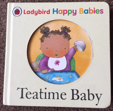 Front cover of Teatime baby book. A plain cream cover with the title on and a big hole in the middle in which you can see the picture on the next page of a cartoon of a baby girl with brown hair sitting in a highchair wearing a purple top holding a bowl up into the air and smiling.