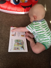 almost bald, blond 8 month old baby in white vest with green crocodiles all over it sitting on a beige carpet in front of a small inflatable ladybird ballpit He is looking at the open Goldilocks book.
