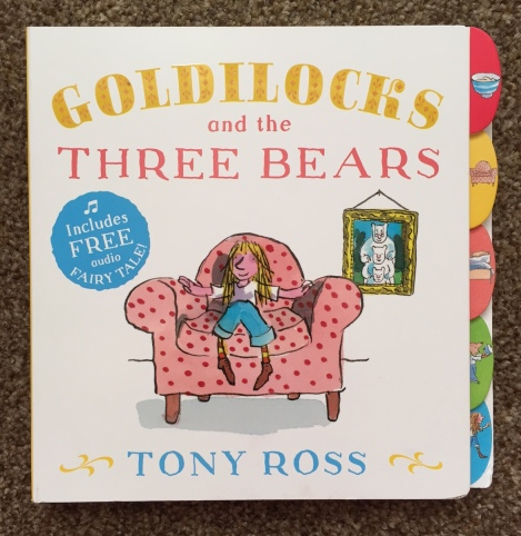 Front cover of Goldilocks book by tony ross. White background with Yellow writing for the title, a Cartoon Goldilocks (blond girl in blue jeans and white top) sat on a pink arm chair with a portrait in the background. There are little picture tabs along the side; a bowl, a chair, a bed, a bear and Goldilocks