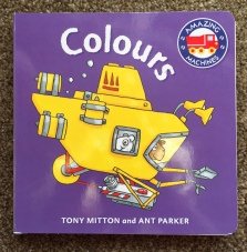 Front cover of Amazing Machines Colours book with a cartoon yellow submarine on the front with some animals inside. this is on a purple background and the title is in white.