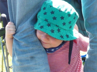 TM (9 month old baby) wearing a green hat with blue stars, a blue bib with pale blue stars and a stripy red vest, holding on to two jean-clad legs and peering round one of them with a little smile