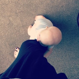 TM (almost bald 8 month old baby in a white vest) clinging onto my leg. I'm wearing black trousers and we are stood on a beige carpet. You can see my toes which are painted purple.