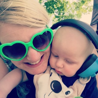 Me ( blonde 26 year old!) wearing green novelty sunglasses and smiling at the camera, TM (bald baby, 6 months old at the time) looking down wearing big blue ear defenders and a brown monkey bib, with his face right next to mine