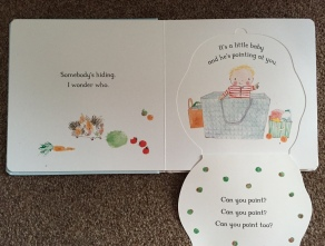 The open pages of a book - white background One side says 'Somebody's hiding I wonder who' and the other side I have opened the flap to show an illustration of a baby boy wearing a red stripy onesie sitting in a shopping bag pointing