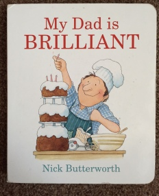 "Front cover of ""My Dad is BRILLIANT"" by Nick Butterworth. Title is in red. Illustration of a man wearing a chefs hat making a big three tiered cake with mixing bowl etc around him."