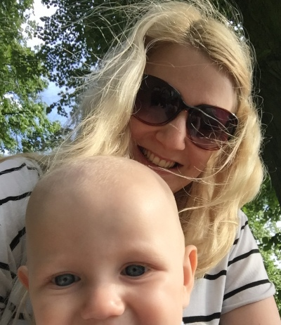 Me (blonde, 26 year old) and TM (bald 9 month old baby) looking at the camera with trees and blue sky behind us. My hair is blowing slightly over TM's head, and the picture is cut off so you can only see the top of his head, his blue eyes and nose. I am wearing sunglasses and smiling at the camera and wearing a white and black stripy top