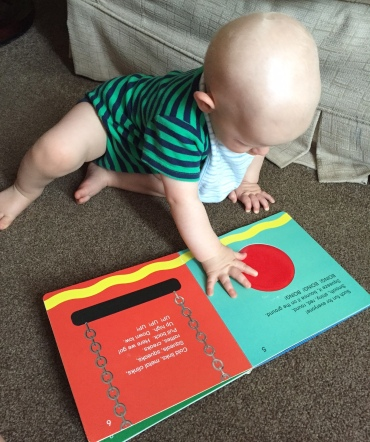 Bald 9 month old baby (wearing green vest with blue stripes and a pale blue stripy bib) sat on a beige carpet in front of a pale beige sofa reading an open book with his hand on one page pushing a big red button. There's a swing on the other page with bright silver chains.