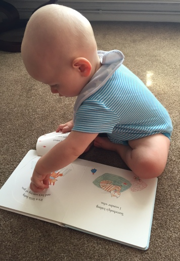 almost bald 9 month old baby (wearing a bright blue and white stripey vest and a pale blue bib with white stars) sat on a beige carpet reading an open book opening a flap and pointing at the page