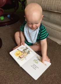 Bald 9 month old baby (wearing green vest with blue stripes and a pale blue stripy bib) sat on a beige carpet in front of a pale beige sofa reading an open book with illustration of a Dad playing musical instruments