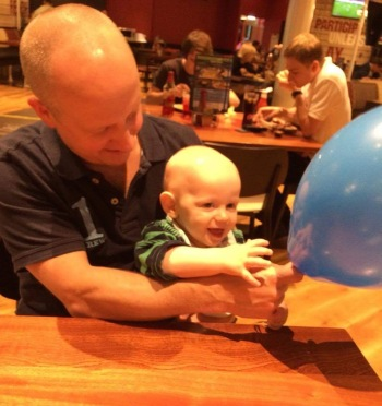 A poor quality photograph! B (40 year old bald man, wearing a blue polo top) is holding TM and a blue balloon. TM (10 month old bald, male baby wearing a green and blue stripy top) is reaching for the balloon and smiling. They are sat at a table in a restaurant.