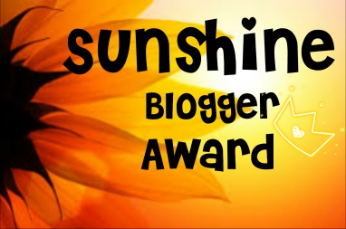 The Sunshine Blogger Award badge - sunflower and sunset in background so lots of yellow and orange with black writing