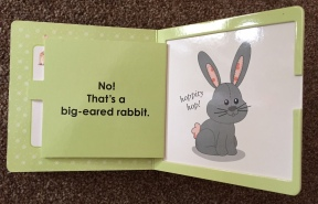 Page of Sophie the giraffe book - green background with an open flap showing a big grey rabbit