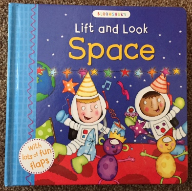 Lift and Look Space front cover. Purple background with a globe, colourful stars, astronauts wearing party hats and animal alien things..