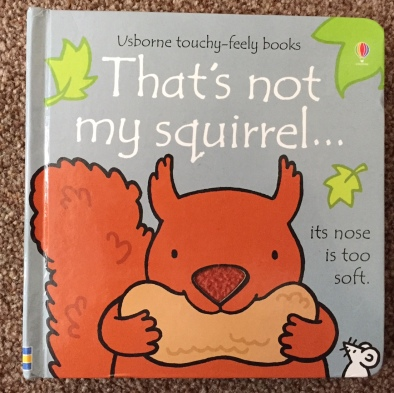Touchy-feely book That's not my squirrel... front cover - a red/brown squirrel holding a nut with a furry nose saying 'its nose is too soft'