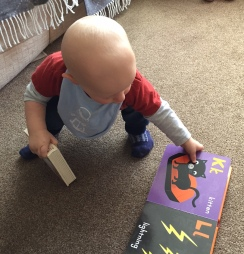 TM (10 month old almost bald baby wearing red and grey top, blue bib, blue jeans and blue and white socks) crouching on a beige carpetted floor with his hands on the open page of the Halloween book - K for kitten and L for lightning. In his other hand is another book but you can't see what it is.