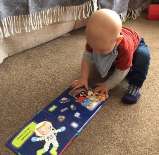TM (10 month old almost bald baby wearing red and grey top, blue bib, blue jeans and blue and white socks) crouching on a beige carpetted floor with his hands on the open page of a Space book. The page is a blue background with an astronaut and a bag full of stuff
