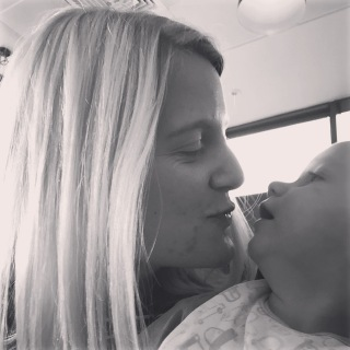 Black and white image of me (blonde, 26 year old) looking at my son pulling a 'kiss' face. TM (side of his face visible, an 11 month old baby wearing a patterned bib) looking at me with his mouth open
