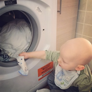 Almost bald, blond 1 year old pulling socks out of the washing machine. He is wearing a green stripy top, jeans and a blue bib with a dinosaur on it.