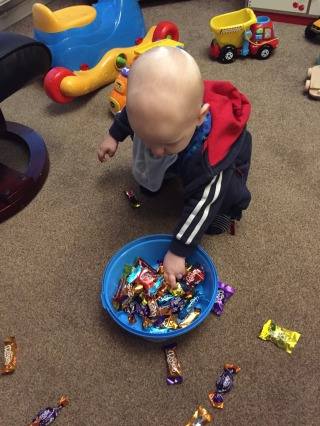 almost bald, blond 1 year old wearing a blue hooded top with white stripes on the sleeve with his hands in a tin of Cadburys Roses, there are chocolates all over the floor and toys behind him. He's on a beige carpet.