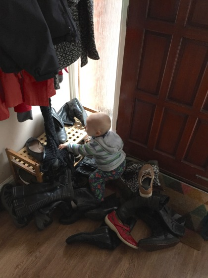 Almost bald, blond 14 month old boy wearing a grey and blue stripe hooded jumper and PJ bottoms with aliens on them is pulling the last few pairs of shoes off a wooden shoe rack. He is surrounding by shoes (mostly black pairs of boots!) and is by a brown front door with a window next to it. There are coats hanging above him.