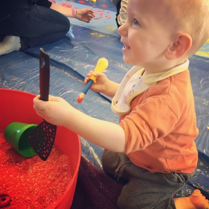 Almost bald, blond, blue eyed 14 month old wearing an orange top, a white bib and grey joggers is sat on a floor at a messy play group. He is holding a yellow and blue paintbrush with red paint on in one hand and a black spatula in the other, hovering over a red bucket with grains of rice and pots in. He is looking away from the camera but smiling.