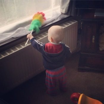 Almost bald, blond 14 month old wearing a blue hoody with a red hood, and blue and red stripy PJ bottoms. Holding a big multicoloured feather duster which he is 'dusting' the windowsill with. The window is above a radiator.