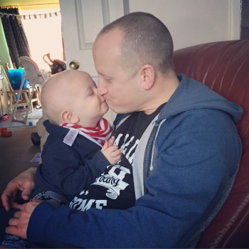 Almost bald, blond 14 month old boy (TM) kissing his Dad (also almost bald!) on the lips . Both wearing blue jumpers. TM is wearing a red and white stripey bib. They both have their eyes closed and a slight smile.
