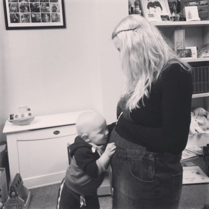Black and white picture of a blonde 27 year old pregnant woman with a bump. Her hair is covering her face as she looks down at her 15 month old son with his hand on her belly going in for a kiss.
