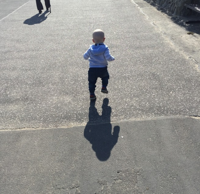 Almost bald, blond 16 month old walking along a big path. The photograph is taken from behind him. He is wearing a grey hoody and blue jeans and is mid-step. You can see his shadow clearly too.