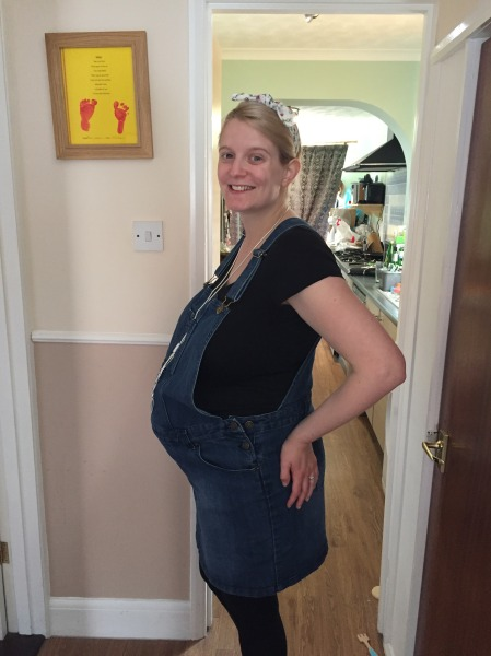 27 year old blonde woman wearing a black top and blue dungarees. Standing in front of a kitchen doorway to the side so you can see a very big 33 week pregnancy bump! Wearing a silver necklace and a white flowery bow in hair which is tied back. Smiling at the camera.