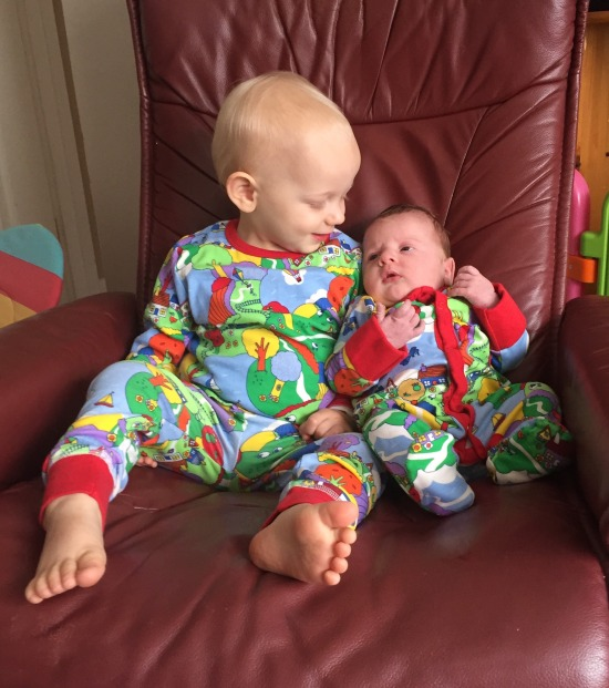 A 20 month old blond toddler (who doesn't have much hair!) wearing bright coloured pyjamas depicting a countryside scene, sat on a big red Lazy Boy chair. He is looking down at his 2 week old brother who is wearing a matching sleepsuit to the pyjamas. The toddler is smiling at his brother. The baby has his eyes open but is looking away from the camera.