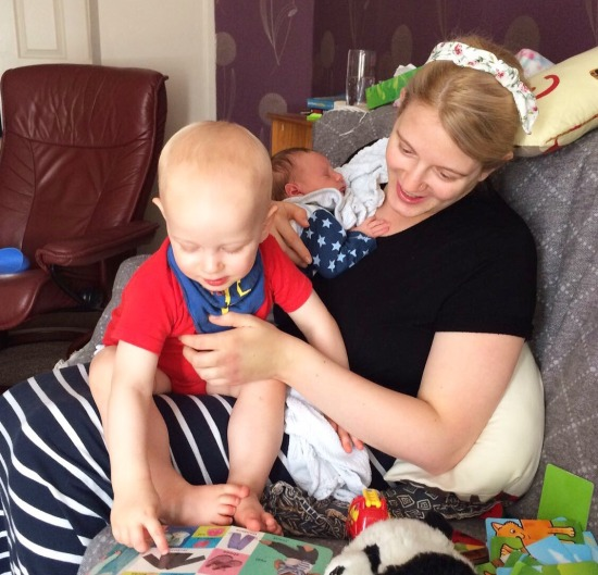 Blond 27 year old woman with her two children. They are sat on a sofa covered in a grey throw, surrounded by toys and books. She is wearing a black t shirt, navy and white long stripy skirt and a flowery headband. She is holding a newborn baby wearing a blue sleepsuit on one shoulder and has a blond 20 month old toddler sat on her lap pointing at a book. He is wearing a red vest and a blue bib.