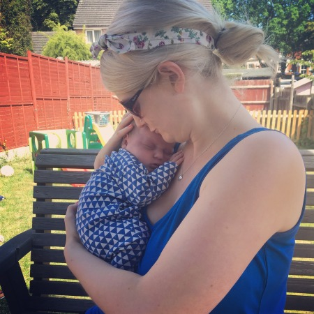 A mum and newborn baby sat on a garden bench on a sunny day. Mum is 27 year old, blonde caucasian with a flowery headband and hair tied in a bun. She is wearing sunglasses and a blue sleeveless top. She is holding her baby, all squashed up and asleep, on her shoulder and kissing the top of his head. He is also caucasian with dark hair and is wearing a blue and white sleepsuit. The photo is taken with them in profile.