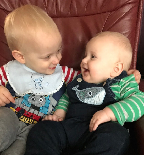A 2 year old boy and 6 month old boy sat on a big red leather chair looking at each other and smiling. Both have blonde hair and quite pale skin. The 2 year old (TM) is on the left and is wearing a thomas the tank engine top, grey trousers and a blue bib with a dog on it. The 6 month old (JB) is wearing a green stripy top with blue dungarees over the top and a whale on it. TM has his arm around JB.